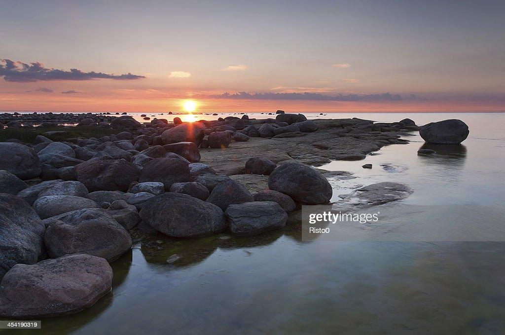 Puesta de sol detrás de rocky coast : Foto de stock