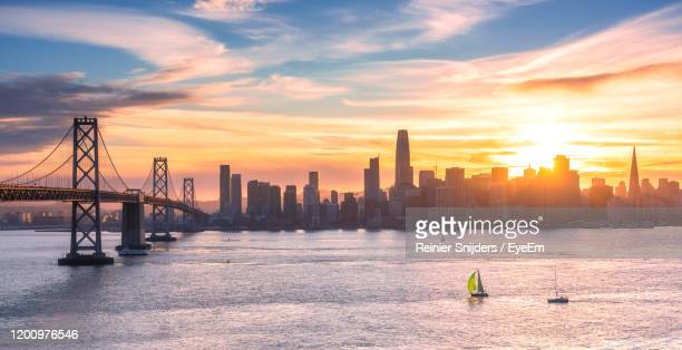sunset behind the san francisco skyline seen from treasure island - treasure island california stock pictures, royalty-free photos & images