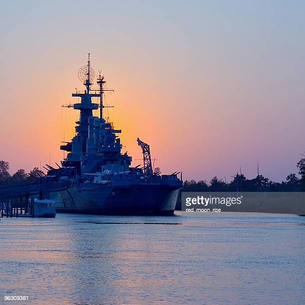 sunset behind uss north carolina - navy ship stock pictures, royalty-free photos & images