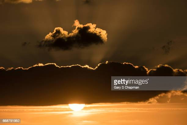 Sunset below silver-lined clouds