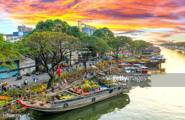 sunset boat dock flower market along canal wharf - south vietnam stock pictures, royalty-free photos & images