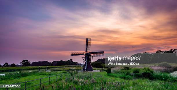 sunset by the mill - lucht stock-fotos und bilder