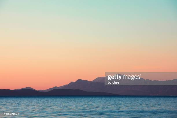 sunset by the sea - mountain range stock pictures, royalty-free photos & images