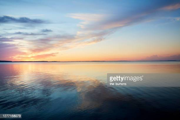 sunset by the sea, the sky is reflected in the sea - abenddämmerung stock-fotos und bilder