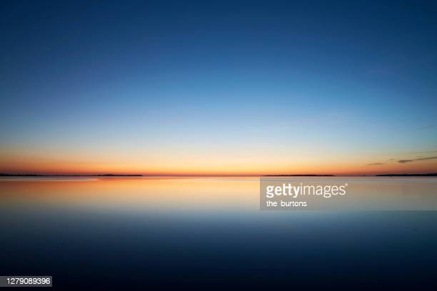 sunset by the sea, the sky is reflected in the smooth sea - romantic sunset stock pictures, royalty-free photos & images