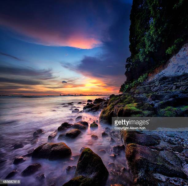 Sunset by the sea with rocks and smooth waters