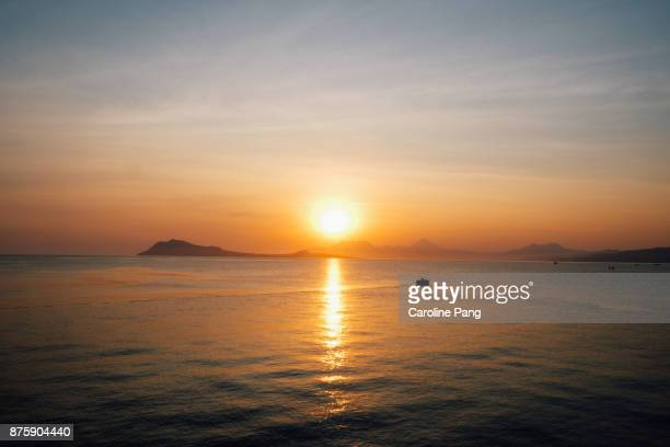 Sunset, calm sea and mountains beyond the horizon as seen from the coast of Ende, Flores, Indonesia.