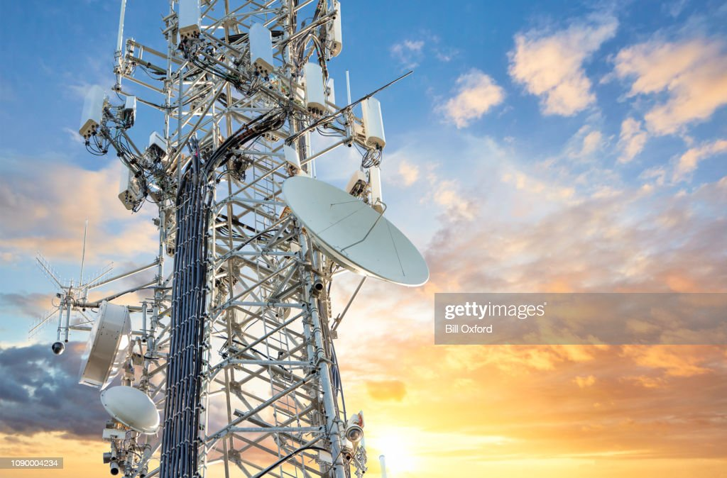 5G Sunset Cell Tower: Cellular communications tower for mobile phone and video data transmission : Stock Photo