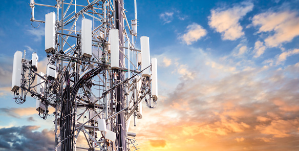 5G Sunset Cell Tower: Cellular communications tower for mobile phone and video data transmission 1090008690