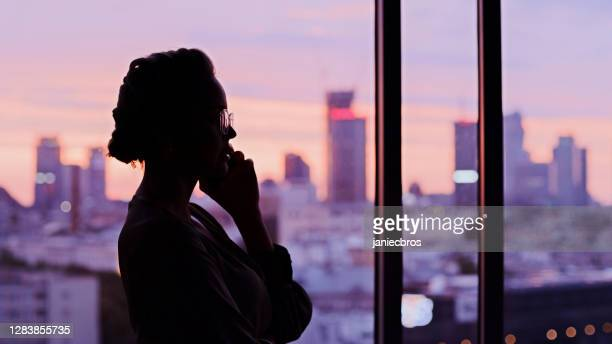 sunset cityscape in office windows. elegant businesswoman's silhouette making a call - in silhouette stock pictures, royalty-free photos & images