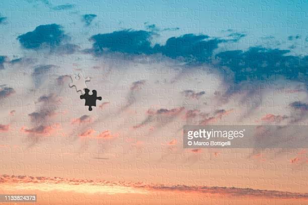 sunset clouds jigsaw puzzle with one missing piece - inachevé photos et images de collection