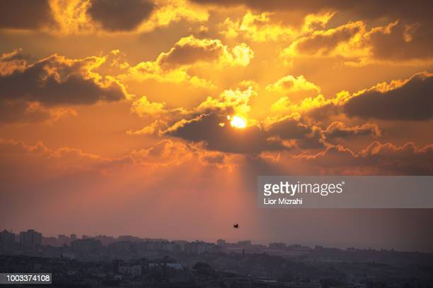 Sunset descends over part of the Gaza Strip, seen from a hill on July 21, 2018 next to Sderot, Israel. A ceasefire was reached between the Israeli...
