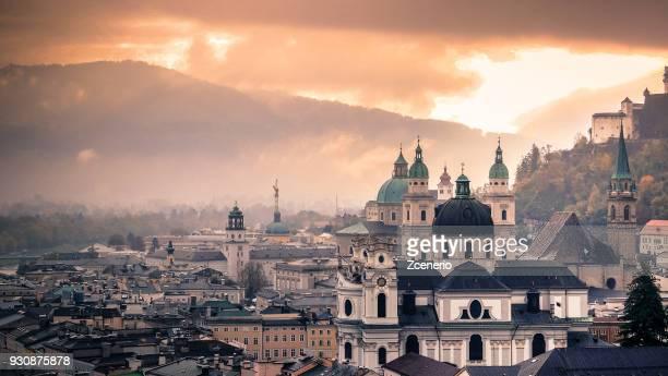 sunset dramatic sky shining over the city of salzburg, austria - salzburg stock-fotos und bilder