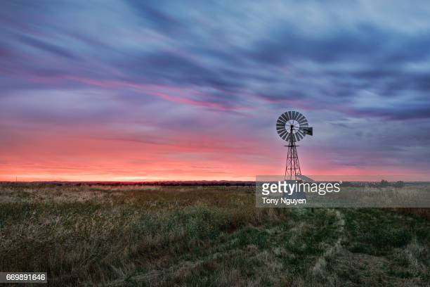 sunset falling behind a windmill. - the karoo stock photos and pictures