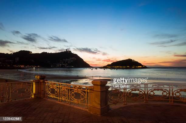 sunset falls over la concha beach - uferpromenade stock-fotos und bilder
