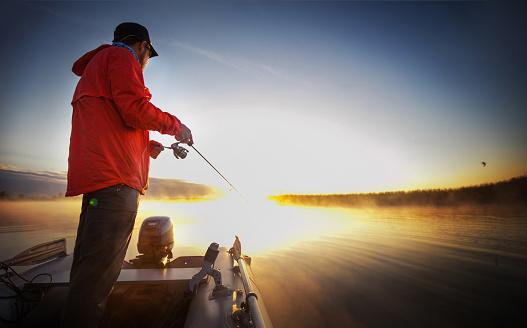 Sunset Fishing. Man fishing on a lake. 897976478