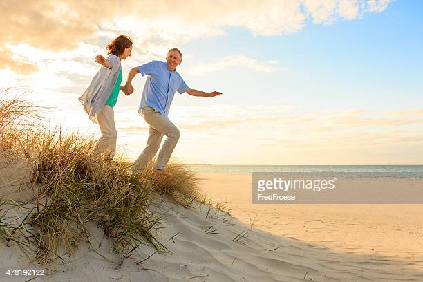 Sunset – happy mature couple at beach