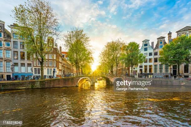 sunset in a canal in amsterdam, netherlands - amsterdam stock-fotos und bilder