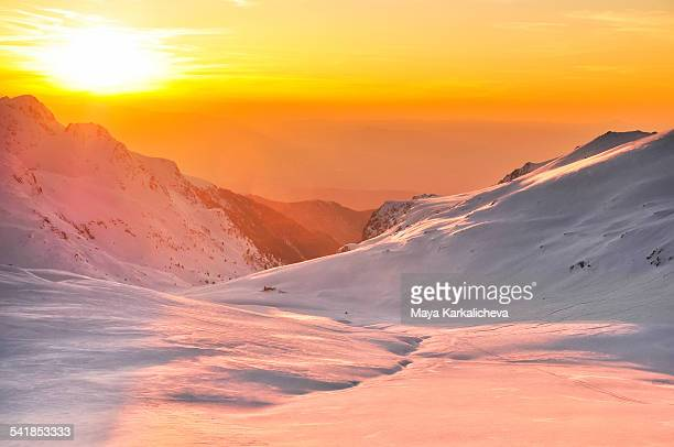 Sunset in a snowy winter mountain valley