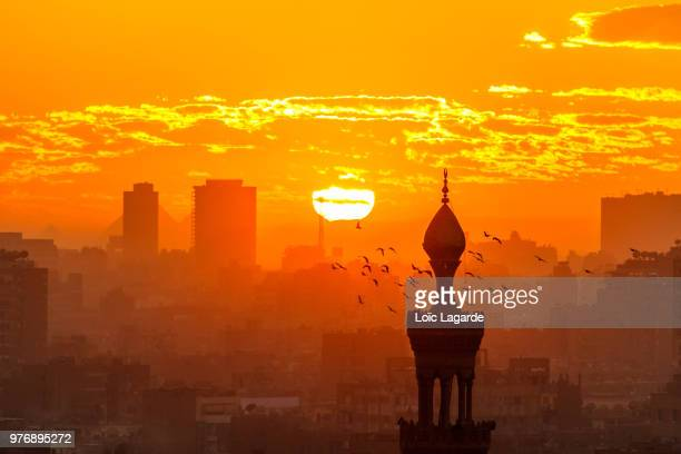 sunset in cairo from al-azhar garden, egypt. the pyramids behind two buildings in background - cairo stock pictures, royalty-free photos & images