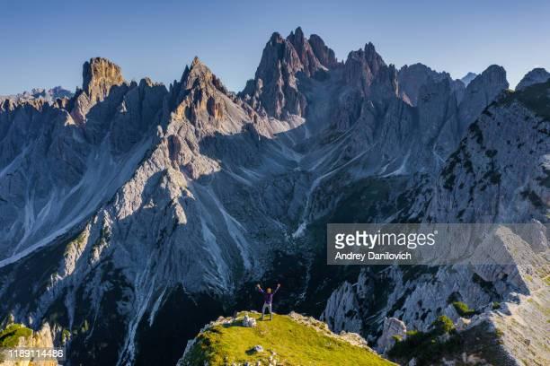 トレ・シメ・ディ・ラザレドの近くにあるイタリアアルプスの夕日。岩の端に立っている男。 - トレチーメディラバレード ストックフォトと画像