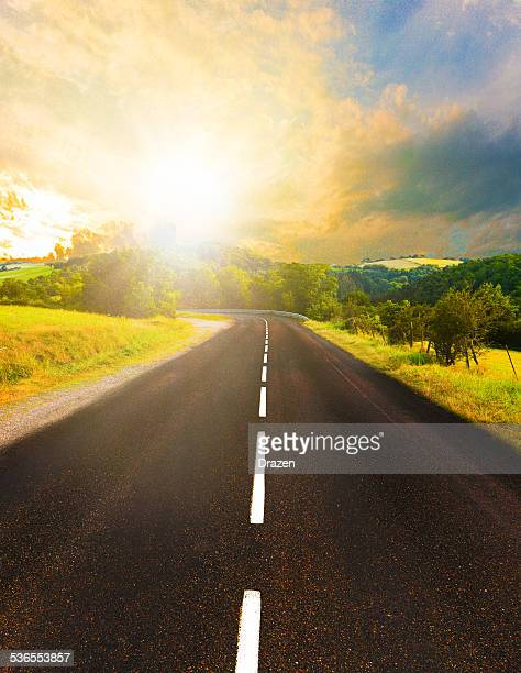 Sunset in nature with endless road leading towards forests