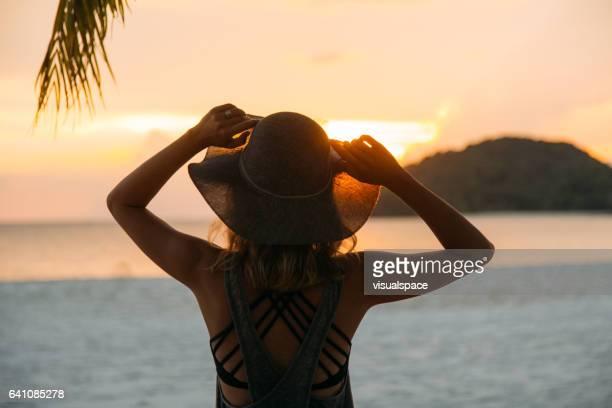 puesta de sol en el paraíso  - chica morena de espaldas fotografías e imágenes de stock