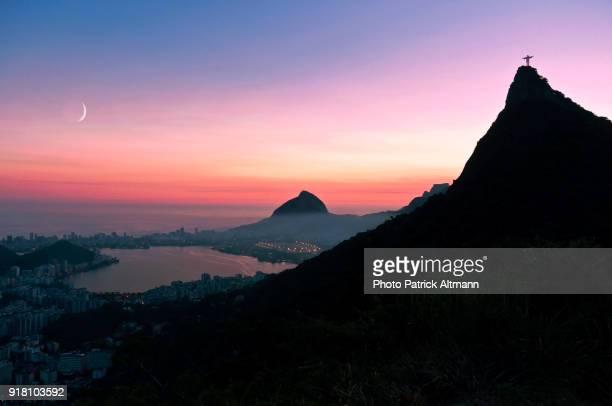 """sunset in rio de janeiro's famed corcovado """"christ the redeemer"""" with pale moon - rio de janeiro photos et images de collection"""