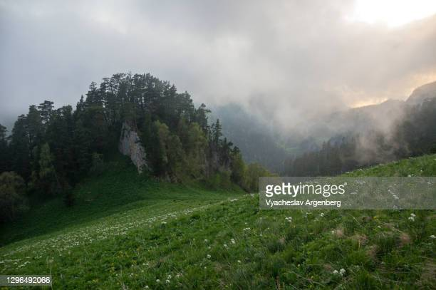 sunset in shisha valley with clouds and fog, caucasus biosphere reserve - argenberg stock pictures, royalty-free photos & images