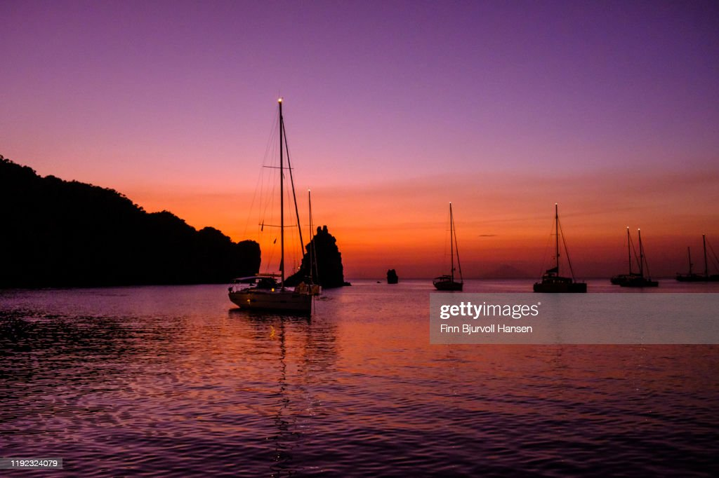 Sunset in the bay of the Aeolian Lipari Island Vulcano with sailing boats against the horizon : Stock Photo