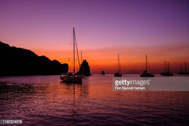 sunset in the bay of the aeolian lipari island vulcano with sailing boats against the horizon - finn bjurvoll - fotografias e filmes do acervo