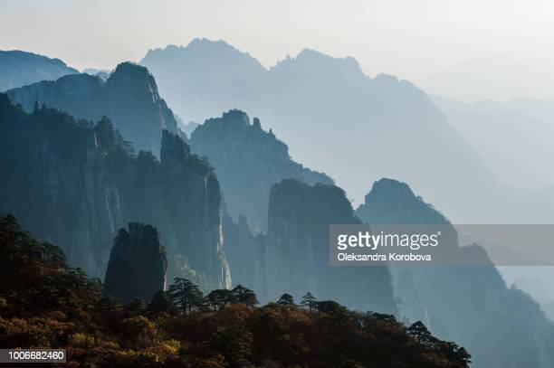 sunset in the huangshan mountain range - anhui province, china. evening sun lights the cliffs below and observation deck. - china east asia stock pictures, royalty-free photos & images