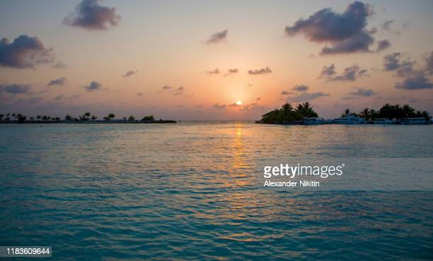 sunset in the maldives. the last boat departs from a small island to male airport. - インド洋 ストックフォトと画像