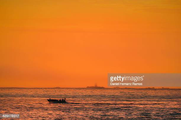 Sunset in the sea in Baiona (Bayona) with a lighthouse in the background. Pontevedra. Galicia