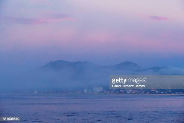 Sunset in the sea with blue clouds an the town of Bayona in Galicia