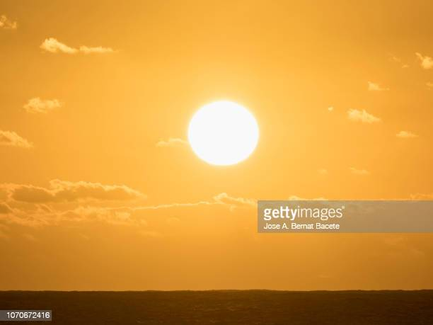 sunset in the sea with clear sky, with high clouds of orange and yellow color. - luz del sol fotografías e imágenes de stock