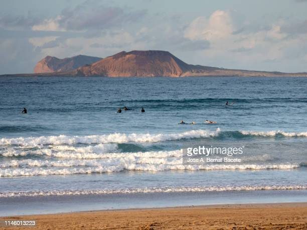 sunset in the shore of a beach with persons practising surf. lanzarote island, canary islands, spain. - lanzarote stock pictures, royalty-free photos & images