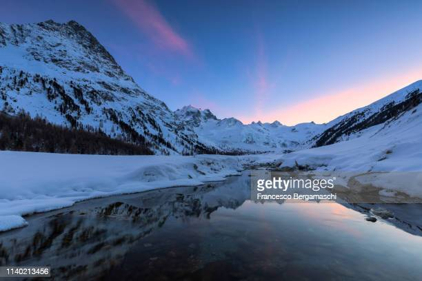 sunset in the val roseg in winter. pontresina, val roseg, engadine, canton of grisons, switzerland, europe. - saint moritz foto e immagini stock
