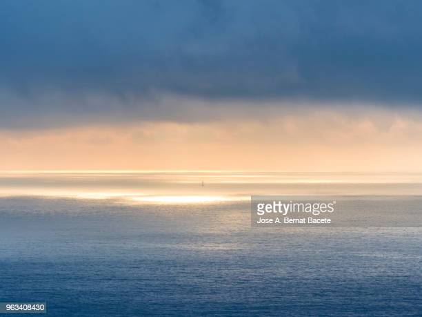 sunset  in the waters of the atlantic ocean, with the silhouette of one a small sailboat, terceira island, azores islands, portugal. europe. - heat haze stock pictures, royalty-free photos & images