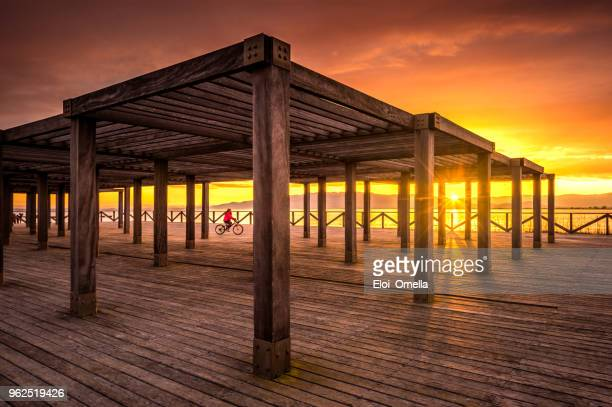 sunset in trabucador beach dock with girl in bicycle - ebro river stock photos and pictures