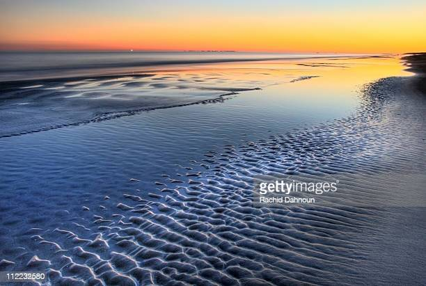 a sunset is reflected at low tide at coligny beach on hilton head island, south carolina. - hilton head stock pictures, royalty-free photos & images