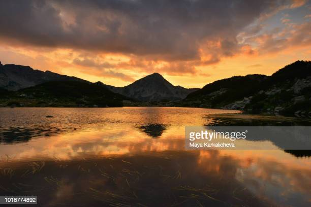 sunset landscape of mountain peak reflecting on calm lake - pirin national park stock pictures, royalty-free photos & images