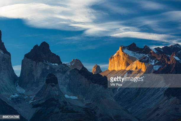 Sunset light illuminates the yellow granite face of Monte Almirante Nieto At left is the East Horn or Cuerno of the Curenos del Paine with Monte...