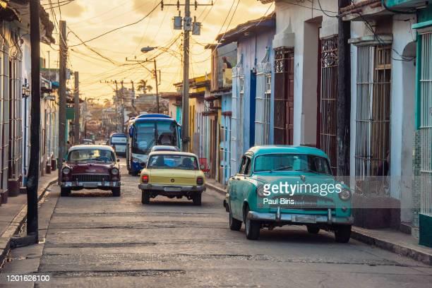 sunset light shining on street with old cars in trinidad, cuba - patrimonio de la humanidad por la unesco fotografías e imágenes de stock