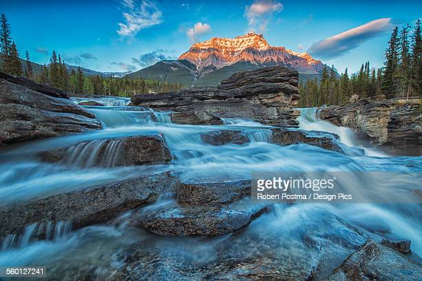 Sunset lights up Mount Fryatt as the Athabasca River flows over Athabasca Falls in Jasper National Park