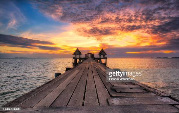 sunset looking over wooden bridge - pier stock pictures, royalty-free photos & images