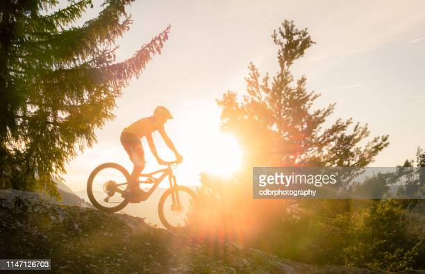 sunset mountain biking silhouette - cross country cycling stock pictures, royalty-free photos & images