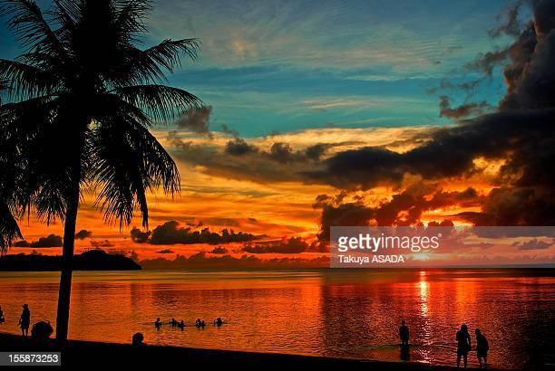 sunset of tamuning beach - guam stock pictures, royalty-free photos & images