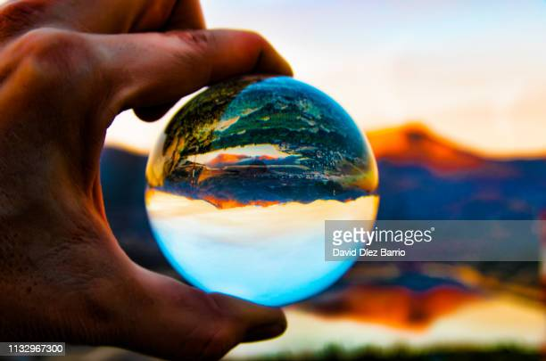 sunset of the mountain 'la maliciosa' reflected in the navacerrada reservoir and all of them reflected in a crystal ball - imaginación stock pictures, royalty-free photos & images