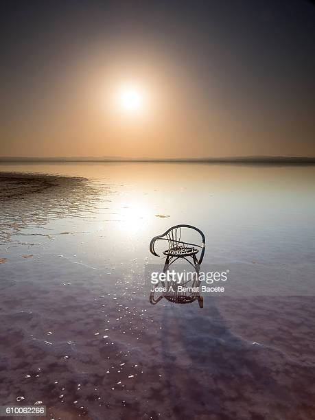 Sunset on a calm lake water pink with a broken wooden chair
